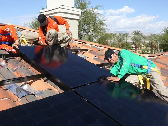 Renova Solar lead installer Ralo Medina, right, installer Pablo Salazar, left, and installer Brandon Gomez attach a new panel to a solar array at a home in Indian Ridge Country Club in Palm Desert on Wednesday, Oct. 8, 2014.