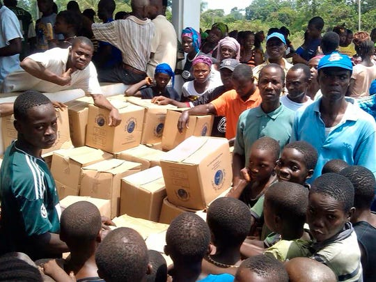 A crowd gathers around the boxes of meals prepared