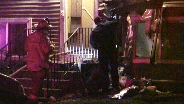 Investigators inspect the fire scene at the Dorsey Garden Apartments in Greece early Friday.