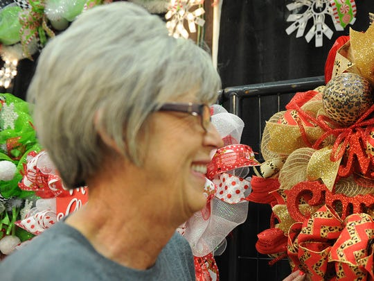 Michelle Kenyon chooses the wreath she wants to take home from Glitter Gypsie's Boutique owned by Tammy Miller at Christmas Magic Saturday, Nov. 5, 2016, at the MPEC.