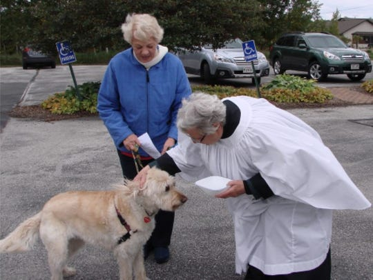 Mother Barb Sajna blesses one of the dogs at St. Luke's.