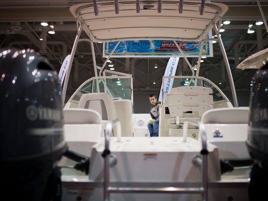 A boy boards a Boston Whaler walkaround as the 32nd