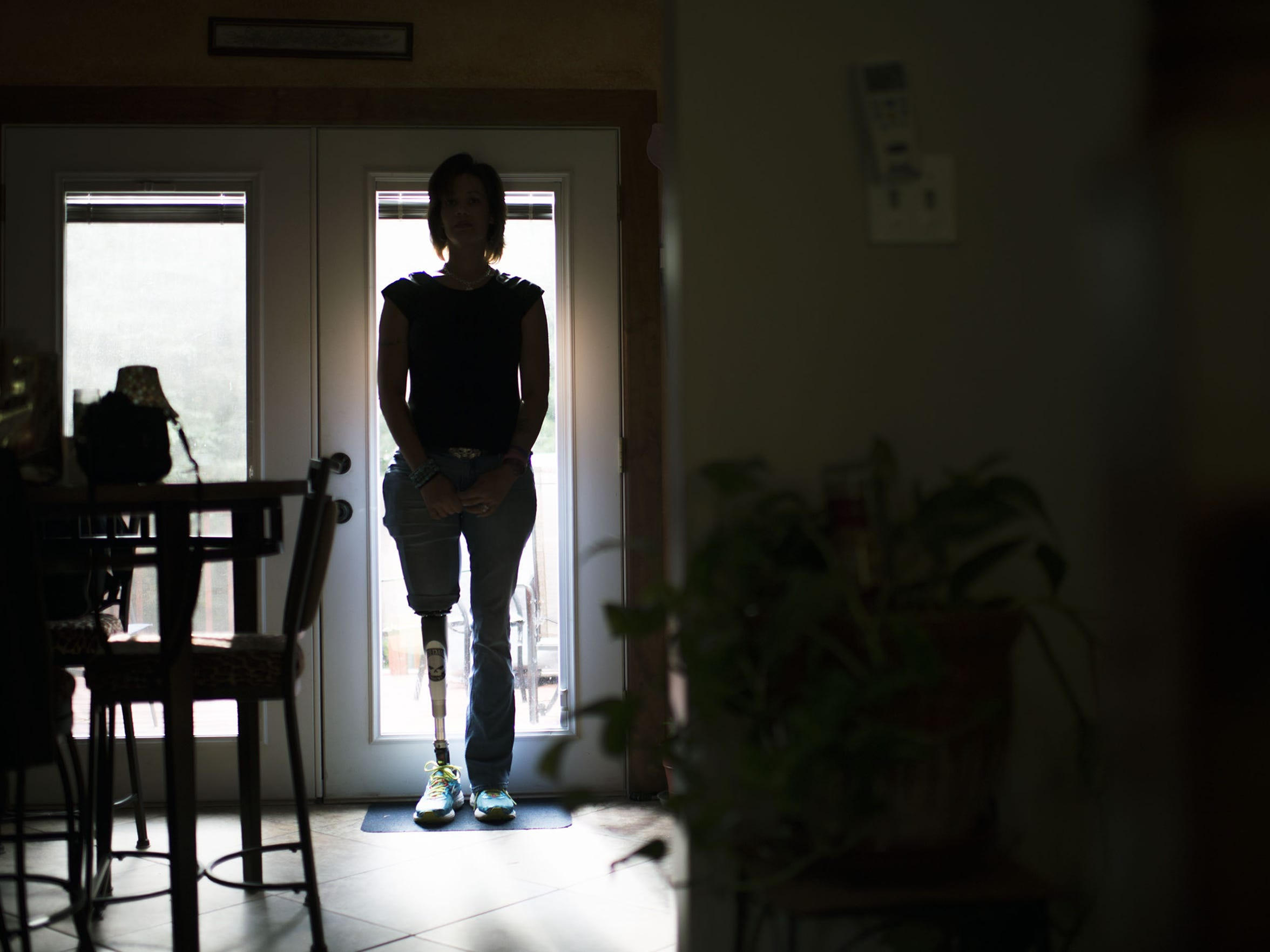 Dishon Tolan is silhouetted inside her home in Newfield.
