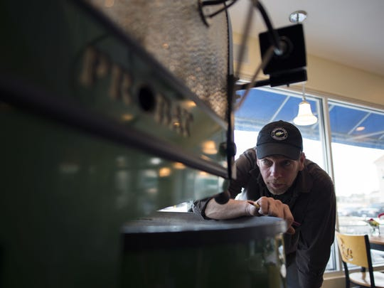 Sean Hixon of The Point Coffee House inspects the flame level inside his roaster at in Rehoboth Beach.