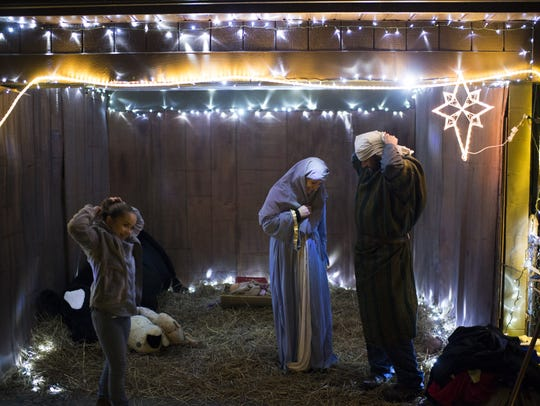 Joan Durham, center, gets in costume inside a nativity