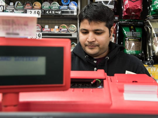 Romin Shah, of Salisbury, prints out lottery tickets for a customer at Vintage Beverages on Snow Hill Rd on Tuesday Jan. 12, 2016.