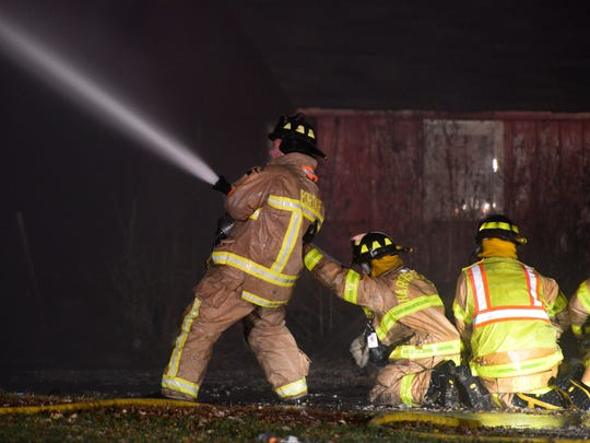 Firefighters from nine area fire departments battle a house fire near the village of Rocky Ridge, about five miles northwest of Oak Harbor in Ottawa County on Thursday, Nov. 12, 2015. Strong winds gusting up to 50 mph made it tougher for firefighters trying to contain the blaze, which engulfed the single-family house at 15645 W. True Road. No one was injured.