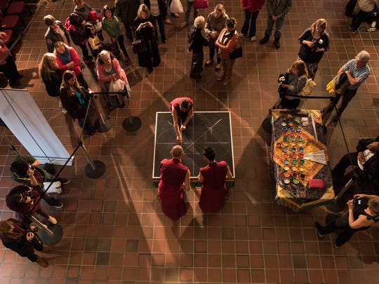 Tibetan Buddhist Monks from the Draping Loseling Monastery of India prepare a Mandala Sand Painting at Salisbury University on Tuesday, April 12, 2016.