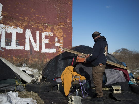A homeless man brings back a donated pizza to his tent by S. 7th St. near the intersection of Mechanic St. on Wednesday, Jan. 27, 2016, in Camden.