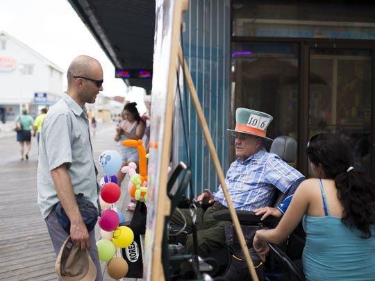 "FILE IMAGE: William Campion, center, sells balloons as the ""Mad Hatter"" on the Boardwalk. Campion is part of a group who represents street performers as they fight with the Town of Ocean City over regulations."