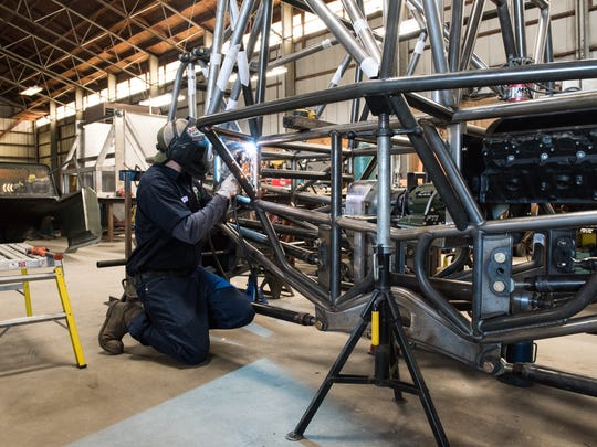 Ryan Disharoon, owner of the Metal Shop, welds a section