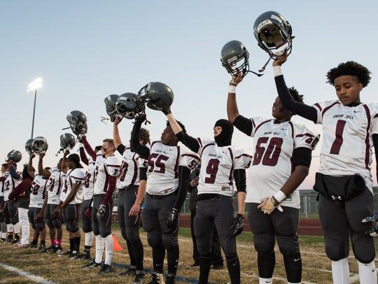 Snow Hill football players raise their helmets after