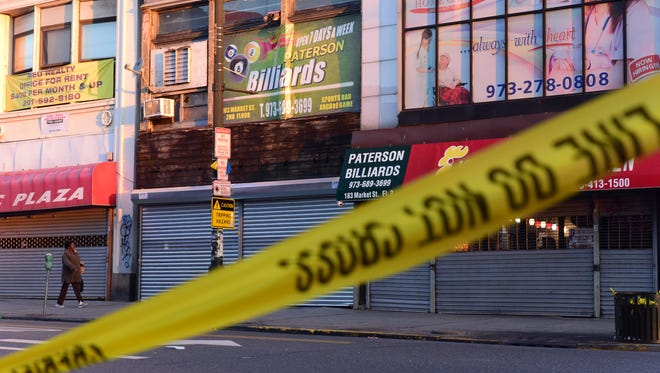 Police crime scene tape is still noticeable after an early morning possible fatal shooting inside a pool hall on the corner of Market St and Church St in Paterson.