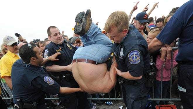 Police officers attend to a Papa Roach fan during the 2011 Carb Day concert.