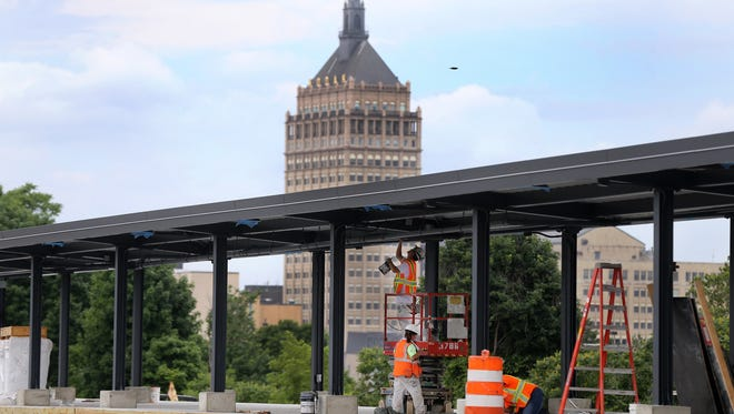 Workers put the finishing touches on the platform area of the new Rochester train station.