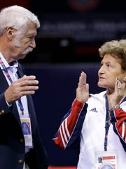 Bela Karolyi, left, and his wife Marta Karolyi talk on the arena floor before the start of the preliminary round of the women's Olympic gymnastics trials, Friday, June 29, 2012, in San Jose, Calif.