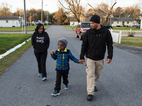Rondell Redding walks with his son Raheem, 9, and his