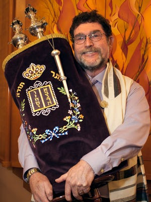 Rabbi Larry Karol of Temple Beth-El poses for a photo with the Torah scroll, the holiest book within Judaism, made up of the five books of Moses, in front of the Ark on Monday, Dec. 14.