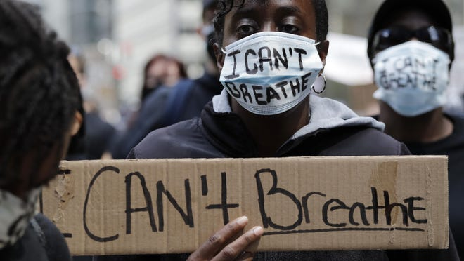 """A person wears a mask reading """"I Can't Breath"""" as she holds a sign during a protest over the death of George Floyd in Chicago, Saturday, May 30, 2020. Protests were held throughout the country over the death of George Floyd, a black man who died after being restrained by Minneapolis police officers on May 25."""