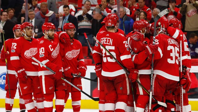 The Red Wings celebrate after the Wings' 3-1 win on Friday, Dec. 15, 2017, at Little Caesars Arena.