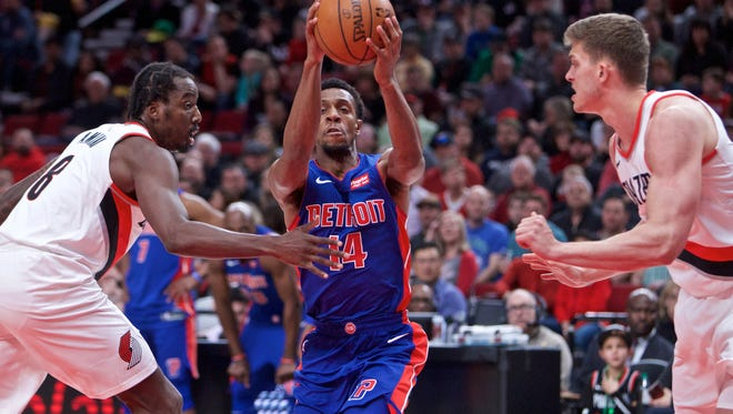 Detroit Pistons guard Ish Smith (14) drives to the basket past Portland Trail Blazers forward Al-Farouq Aminu (8) and center Meyers Leonard (11) during the first quarter at the Moda Center on Saturday, March 17, 2018.