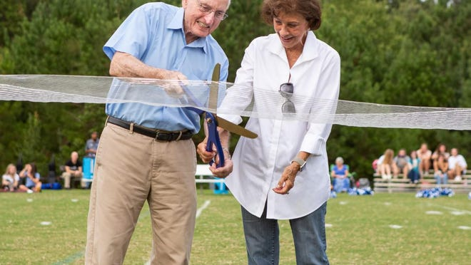 Former UGA football head coach Vince Dooley and wife Barbara Dooley cut a ribbon during a ceremony naming Monsignor Donovan's football field after the family.