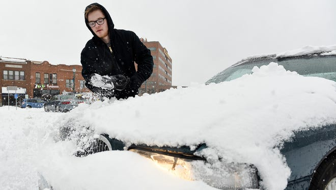 Christian Carls scrapes the ice and snow off his car after work Monday, March 5, in St. Cloud.