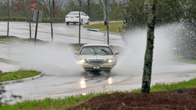 A motorist drives along flooded Hugh Ward Boulevard in Flowood on Friday morning. Days of heavy rain have left roadways across the state flooded, and more rain is on the way.