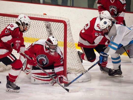 South Burlington's Mason Fay, right, has a shot saved at the post by Champlain Valley goalie Logan Cody during Saturday's boys hockey game at Cairns Arena.