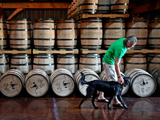"""Lee Kennedy walks with his dog """"Scout"""" past rows of aging whiskey barrels at Leiper's Fork Distillery, part of the Tennessee Whiskey Trail which officially launches June 19. It's a 25-stop tour across the state that's expected to be a major tourism draw similar to the Kentucky Bourbon Trail."""