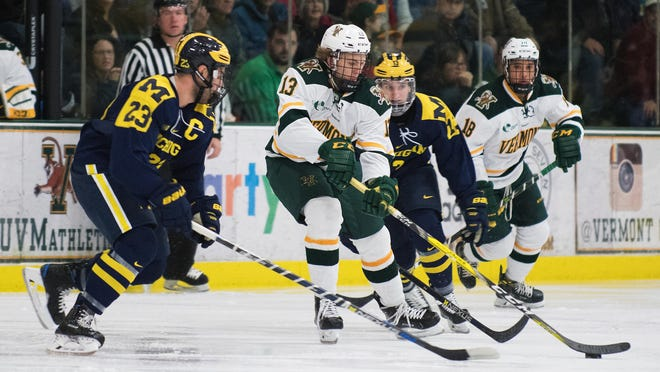 Catatmounts forward Liam Coughlin (13) skates with the puck past Michigan's Alex Kile (23) during the men's hockey game between the Michigan Wolverines and the Vermont Catamounts at Gutterson Field House on Friday night October 28, 2016 in Burlington. (BRIAN JENKINS/for the FREE PRESS)