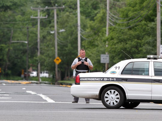 A Howell Township police officer blocks access to Squankum-Yellowbrook Road at Lakewood Farmingdale Road in the township Tuesday afternoon, June 7, 2016.  The road is closed between this intersection and Preventorium Roads for police activity.