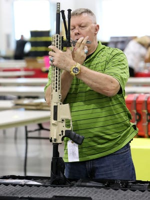 Tim Taconi with A-TAC Arms sets up one of the company's long distance rifles for display, Friday, Aug. 28, for the Fort Smith Gun and Knife Show Saturday and Sunday at the Kay Rodgers Park Expo Center. Sponsored by High Caliber Radio, the event features ammo of all calibers, pistols, rifles as well as vendors with all accessories for shooting. Open 9 a.m. to 5 p.m. on Saturday, and 9 a.m. to 4 p.m. on Sunday, with two-day adult admission costing $10 and children under 10-years-old attending for free with paid adult. Bring a firearm or show your concealed-carry permit, military or veteran I.D. and get $1 off.