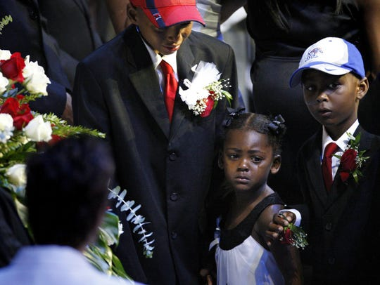 Lamar Wright, Sofia Wright and Lawson Wright grieve the death of their father, Lorenzen Wright, at a public memorial at the FedExForum on Aug. 4, 2010.