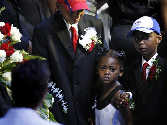 August 4, 2010- (left to right) Lamar Wright, Sofia Wright, and Lawson Wright, grieve the death of their father, Lorenzen Wright, at a public memorial held at the FedExForum.