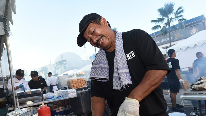 The Team Dokgnos butcher Oliver Malacas slices meat during the 2017 Champion Grill Master competition at the Fifth Annual Guam BBQ Block Party in Tumon on July 1, 2017.