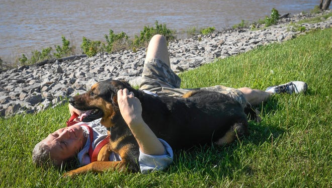 Taking advantage of a little sunny weather, Charles Downer relaxes in the grass with his dog Nemo at Henderson's Red Banks Park on Tuesday. Never fear: the forecast calls for another stretch of pleasant weather starting on Sunday.