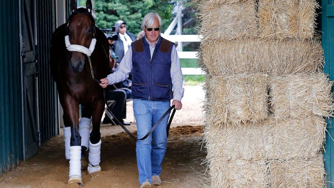 Horse trainer Bob Baffert walks American Pharoah inside the Preakness Barn after arriving for the 140th Preakness Stakes at Pimlico Race Course.
