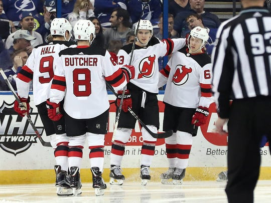 New Jersey Devils center Nico Hischier (13) is congratulated by teammates as he scores a goal against the Tampa Bay Lightning during the second period at Amalie Arena on Saturday, Feb. 17, 2018.