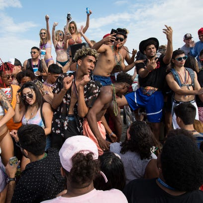 A spring breakers dance on the beds of pickup trucks