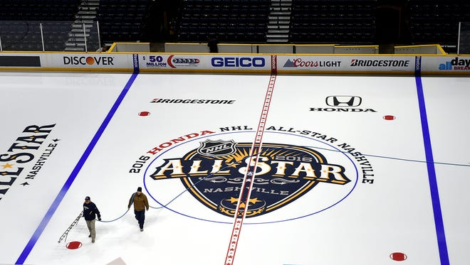Workers spray water to create layers of ice on Monday for the 2016 NHL All-Star Weekend at Bridgestone Arena.