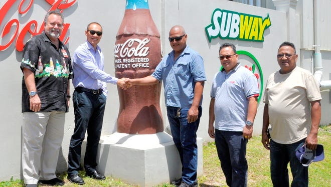 Marcos W. Fong, second from left, CEO of Coca-Cola Beverages Co. (Guam) Inc. and Foremost Foods Inc. and Liyon Sulog, third from right, CEO of the 2018 Micronesian Games, seal the beverage partnership between Coca-Cola and Foremost and the Micronesian Games with a handshake at the Coke and Foremost corporate headquarters in Barrigada Heights, Guam. They are joined by, from left: Mike Brown, regional sales director; Rusty M. Loyola, import/export manager; and Lukas Ruuemau, president of Pacific Bus Company.