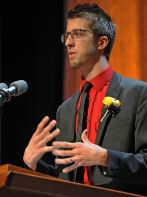 McCutcheon teacher of the year, Jacob Gobrogge, implores the graduates to live their lives in the present tense Sunday at Elliott Hall.