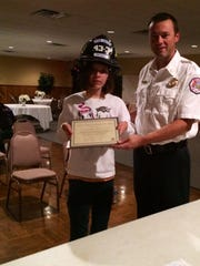 Jenna Toy, 14, stands with Star Cross Volunteer Fire Company Chief Dave Deegan III. Jenna was sworn in as an honorary firefighter last week