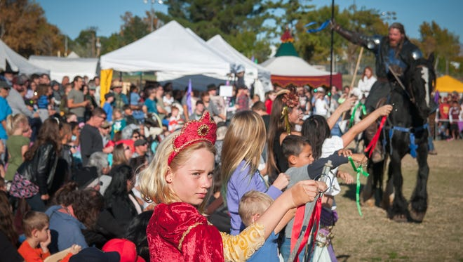 Attendees to a joust hold up ribbons for riders to collect during the 44th annual Renaissance ArtsFaire at Young Park.