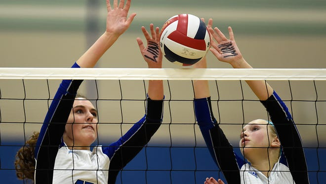 Green Bay Notre Dame's Tera Leonhard (13) and Grace Campbell (8) team up to block a shot made by Bay Port's Dakota Kropp (4) during Thursday night's volleyball game at Green Bay Notre Dame Academy.