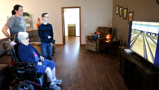 Emily Bresser (standing) watches Suzanne and Andrew play Wii bowling at their Sadoff Group Home in Fond du Lac. Professionals say that developmentally disabled populations can benefit from exergaming, or playing video games as a form of exercise.