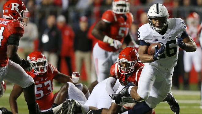 Penn State running back Saquon Barkley (26) runs through the Rutgers defense on Saturday night at High Point Solutions Stadium in Piscataway.