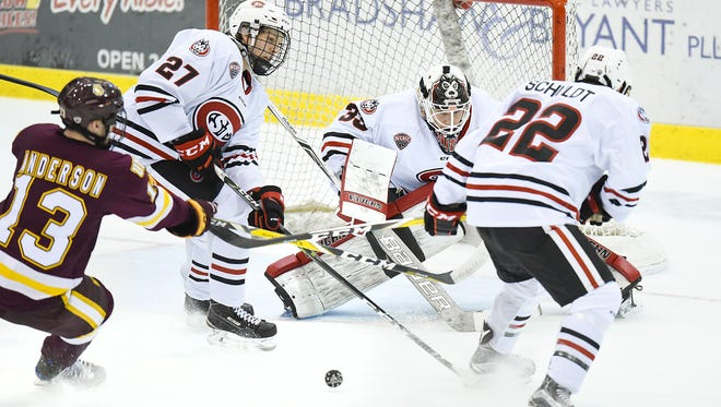 St. Cloud State goalie Zach Driscoll deflects a shot against Minnesota-Duluth this season with defensemen Dennis Cholowski (27) and Jimmy Schuldt (22) looking to clear the puck at the Herb Brooks National Hockey Center. The Huskies are 8-7-1 at the break and hopeful for a strong second half.