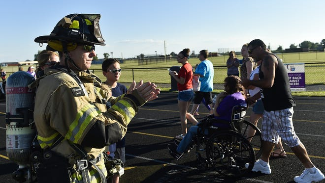 Marion City Firefighter P.J. Titus applauds during the 2016 Relay for Life as cancer survivors walk by  at River Valley High School Friday.